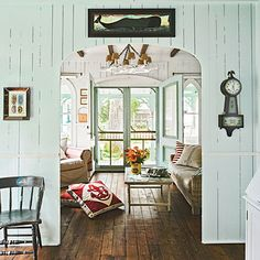 "This small Victorian cottage is full of clever small-space ideas and coveted coastal artifacts. ""I love the nautical touches—they add just the right amount of fun without going overboard. The whale painting above the curved doorway and the bright anchor pillows are guaranteed to bring a smile to your face."