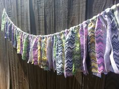 Fabric garland made with soft, thicker cotton fabric. It is made with green, yellow, gray, pink, and purple chevron fabrics. Fabric is untreated so it has some fray to it.  Great for party decor or room decor. Can be used on the bottom of beds or cribs, around the base of a table, or hung on the wall as a banner.  Many cute and wonderful ideas.  The fabric pieces cover 5 feet if placed together (as seen in the image). They can be easily slid down the hemp line though if you wanted to space…