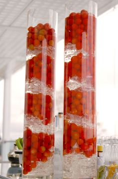 Glass cylinders filled with fresh red tomatoes, cellophane and water to magnify its contents.