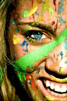 spattered of paint colours in the face .. a pretty girl with a beautiful smile :)