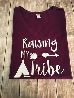"""A Gorgeous Plum Color V-Neck Short Sleeve style shirt embellished with White GLITTER vinyl and our """"Raising My Tribe"""" design. Fit: These are a ladies fitted shirt- if you do not like ..."""