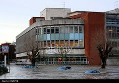 Guildford, Surrey, UK. 24th December 2013. Rising flood water from the River Wey envelops cars in the Millmead Car Park with the Debenhams department store in the background. © Bruce McGowan/Alamy Live News