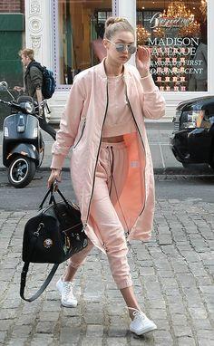 Gigi Hadid usa look comfy de conjunto de moletom rosê com tênis branco, bolsa preta e óculos Dior