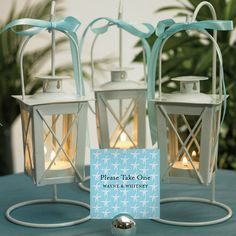 Mini hanging lanterns add a romantic warm glow to your beach, nautical, barn or rustic theme wedding. Pair them with sea shells and sand.