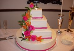 Bright, colorful wedding cake with pink and orange cascading flowers from Candy Haven in Denton