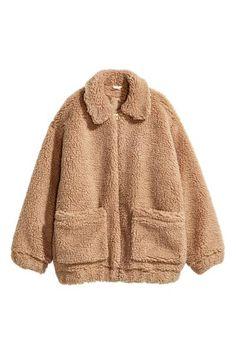 Een korte jas van zacht teddy met een kraag, een blinde ritssluiting en opgestikte zakken. De jas heeft elastiek aan de onderkant en onder aan de mouwen. Ge
