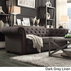Add graceful seating to you home with this Chesterfield sofa by TRIBECCA HOME. Showcasing a tufted back and rolled arms in dark grey linen, this elegant padded seat sofa can provide plenty of support and comfort in style.