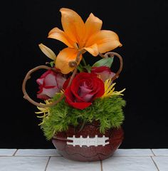 A variety of flower arrangements created in a football container, for the sports enthusiast, high school, college player, or for superbowl parties from Rittners Floral School, Boston, Ma  www.floralschool.com