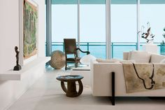 Darryl Carter - Modern Condo Design for his parents in Bal Harbour, Florida - The living area features a custom-made sofa, an antique armchair, a mid-century iron sculpture, and a cocktail table by Brueton. A custom-made shelf holds a painting by Purvis Young and a sculpture by Claudio Barake, and the rug is from Stark.