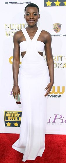 Lupita Nyong'o: 2014 Critics' Choice Awards  The 12 Years a Slave star wore a custom-designed dress by Francisco Costa for Calvin Klein Collection. The beaming beauty paired her look with a gold box clutch by Calvin Klein.  Read more: http://www.usmagazine.com/red-carpet/lupita-nyong-o-2014-critics-choice-awards-2014171#ixzz2qrSjdtfn