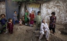 Afghan refugee children react while gathering in an alley of a slum on the outskirts of Islamabad, Pakistan, Tuesday, Oct. 4, 2011. (AP Photo/Muhammed Muheisen)