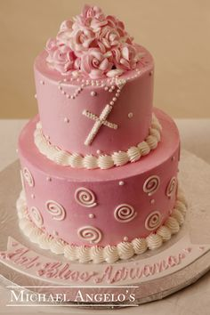 Bright Pink with Roses #24Religious This is a two-tier cake design iced in buttercream and accented with our popular swirl and polka dots. The top is beautifully decorated with buttercream roses. A rosary is piped on and lays over the top for the perfect religious appeal.