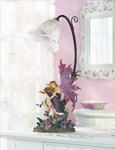 Pausing above a newly blooming bed of violet-sunset orchids, a winged beauty reflects upon the peacefulness of her shady forest glade.  A gorgeous table lamp of incredible artistry, from the graceful floral shade to the delicate lifelike blooms at the base.  Sure to be the pride and joy of any dreamer at heart!