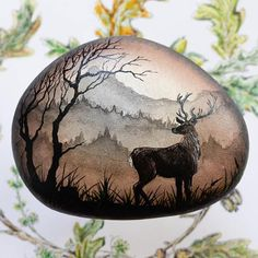 This unique and original fine art acrylic painting of a powerful and majestic stag waiting on the edge of the forest. It is Painted by hand on a naturally tumbled stone from the Irish Sea. Each painted image is done entirely by hand. These are not airbrushed but entirely painted using