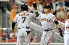 WASHINGTON, DC - AUGUST 22: Joe Panik #12 and Gregor Blanco #7 of the San Francisco Giants celebrate after scoring in the eighth inning against the Washington Nationals at Nationals Park on August 22, 2014 in Washington, DC. San Francisco won the game 10-3. (Photo by Greg Fiume/Getty Images)