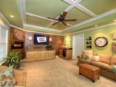 A family room features polished wood on the far wall, with browns on the rug and sofa breaking up the green hue of the walls and ceiling.