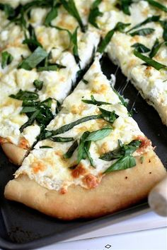 Four cheese white pizza with fresh basil, thyme, and oregano.