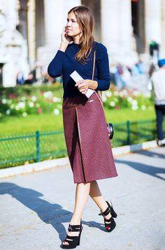 Midi skirt with leather trim paired with a blue crew neck sweater and platform heels