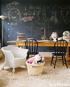 "A space just for the little ones! In Ruby Beets's East Hampton house, Benjamin Moore's blackboard paint covers her daughters' playroom walls, ready when inspiration strikes. The black Farmhouse chairs are from Pottery Barn Kids and the worktable is from Ikea, its legs cut down to child-size. ""When the girls have their friends over, they're not far away, but they can do their own thing without being too with us,"" she says. ""They have their table where they can draw, and a little sofa. They…"