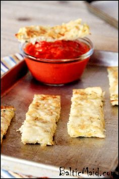 Cauliflower Breadsticks Process the cauliflower in a food processor until it is very finely ground. Place the processed cauliflower in a bowl. Add the eggs, grated garlic, and 1/3 cup of cheese. Season to taste with herbs and spices of choice and salt and pepper.Spread the mix on a baking sheet lined with parchment paper.