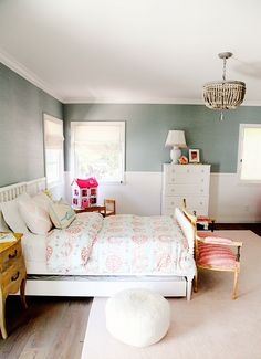 Children's bedroom with light blue and pink patterned bedding, white bed frame,  colorful pillows, wood floors, pink rug, white cabinets, chandelier, and light green walls