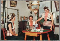 Spakenburg In de Korporaal. 3 moderne vrouwen in traditioneel interieur. 1970-1990. Poserende vrouwen in moderne zomerdracht. Onder wit gebloemde kraplap met gedeelde rode doek dragen zij mouwloos truitje, zonder boormouwtjes. Op schort rood geruit stukje. Zij zitten in traditioneel interieur (mogelijk museumopstelling) om Spakenburger tafel met tinnen kraantjeskan en daarboven olielamp met kralenfranje.  #Utrecht #Spakenburg