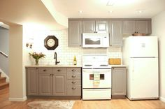 Using the existing white appliances and working with an approximately 12 foot wall, we were able to create a small, country style kitchen with classic white subway tiles, quartz counter-top, and bronze coloured hardware and faucet.