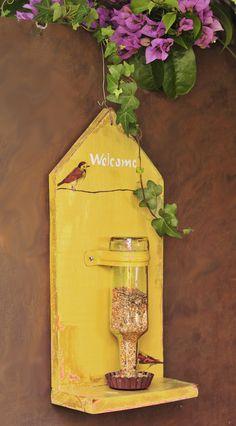 Comedouro para Passaros com Garrafa Cor: amarelo material: produtos reciclados acabamento: pintura fria, decoupage e verniz medida: 40cm X 20cm