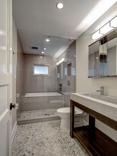 The tub in this Brooklyn, N.Y., guest bathroom is enclosed within a glassed-in shower space, creating a unique bathing area with showstopping style. Gray marble tile in a repeating pattern continues into the shower, drawing the eye forward and visually expanding the space.