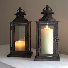 Vintage style metal lanterns for all seasons. Great for use in the home and garden for a welcoming glow for visitors.Create lovely evening candlelight with a few of these lanterns scattered around the home and patio. Perfect for pillar candles for long lasting lighting. Each lantern has a glass surround set within a metal frame with fretwork top vent and handle for carrying or hanging. Distressed metal finish gives a lovely vintage feel. Sold in units of one.Glass and metal.D15cm x W15cm x…
