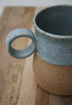 This rustic wheel thrown mug is a new color addition to my new collection of functional ceramics designed to be sturdy for everyday use but with mindful creative elements to engage the user. The true beauty of the stoneware clay is emphasized by placing contrasting raw unglazed clay against the blue speckled glaze. Rustic, simple lines & minimal design for the modern tea or coffee drinker. The lower section is raw/unglazed speckled clay which has a grainy roughness giving a lovely contrast…