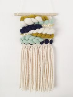 """This mini weaving features an ivory base with mint, navy, chartreuse, and  ivory roving. This weaving also features a gold ribbon detail. Hung on a  wooden dowel, this piece measures approximately 6"""" wide and 17"""" long.This  item is made to order, please allow four weeks for creation and delivery.  Shipping is available to the U.S., International shipping available for an  additional charge."""