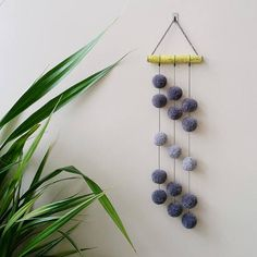 Amazing pompon wall hanging with handmade acrylic pompons hanging by a cotton cord. Length 22.83 (58 cm). Width of wooden stick (oak) 6.10 (15,5 cm). Diameter of pompons 1.57 (4cm).