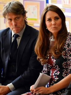 Catherine, Duchess of Cambridge (R), sits with British comedian John Bishop (L) as she listens to speeches during her visit to The Willows Primary School, Wythenshawe to launch a new school counseling program on April 23 in Manchester, England. The Duchess of Cambridge met staff and volunteers, teachers and parents at the school as she launched the program which is a partnership between the Royal Foundation, Comic Relief, Place2Be and Action on Addiction.