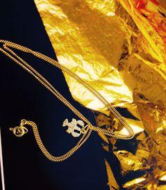 Zlatý přívěsek s řetízkem, na pozadí zlatá folie (Au)