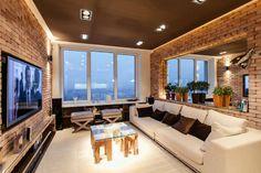 Salon zaaranżowany w neutralnych barwach bieli oraz brązu wzbogacony cegłą na ścianie oraz dużym lustrem powiększającym...