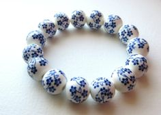 Don't know about you, but we're so ready for spring.   Made with white ceramic beads and hand painted with a blue floral design, this fresh springtime bracelet will definitely leave you yearning for a picnic in the park.   Bracelet is double-strung with high-quality gossamer elastic for extra...