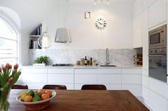 Kök från Ballingslöv med vita snickerier, bänkskiva och stänkskydd i Carraramarmor, blandare från Tapwell och exklusiv köksfläkt med fjärrkontroll från Eico.