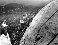 Drillers, suspended in slins fastened with cables to the winches at the top of the mountain, work on the George Washington head of the Mount Rushmore Memorial in the Black Hills area of Keystone, S.D. on July, 22, 1929.