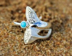 Sterling silver whale tail ring featuring the fluke of a mother humpback whale overlaid with the smaller fluke of her calf and set with a genuine turquoise stone.