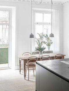 Interesting art in a stunning kitchen. Trendy pale wood dining room.