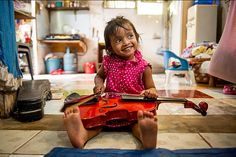 Jilan plays her older brother's violin in her family's living room in Banda Aceh, Indonesia. She was born after the tsunami. Ann Hermes
