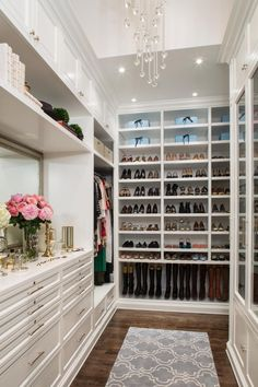 A beaded chandelier is like the icing on the cake in this glamorous, efficient and enviable master closet in London. Cabinetry and shelving extend to the ceiling to maximize storage, and customized compartments hold everything from jewelry to boots to hats to dresses, keeping the transitional space organized and efficient.