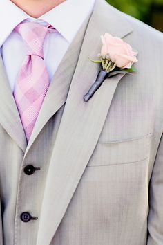 A pink rose makes a lovely boutonierre that complements the groom's pink tie and grey suit. Wedding Flowers: Mandy Scott Flowers