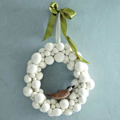 """Felt puffs from your local craft store, glued or pinned  onto a foam wreath form make for a great """"Snowball Wreath."""" Or you can buy this one (available in two sizes, ranging from $40-60, from West Elm 