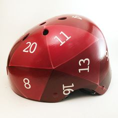 Always use your helmet to leverage your bike ride's probability of success! This icosahedral helmet resembles a twenty-sided die most commonly used for DnD. A classic red and turquoise D20 is featured