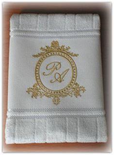 Toalha de lavabo bordada com brasão e monograma dos noivos.    TAMBÉM TEMOS DIVERSOS MODELOS DE BRASÃO DISPONÍVEIS, consulte-nos!    Tamanho aproximado do bordado, 10 cm de altura.    Toalha aveludada 100% algodão, marca Dohler    Embalada em saquinho transparente e laço de cetim (foto).    Dispo...
