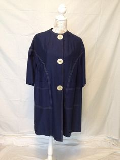 A plus sized 1960's navy 3/4 sleeve raincoat with oversized lucite buttons. Just adorable!