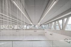 The interior spaces have a monochromatic grey and white palette. Exposed concrete covers the walls and adds a textural quality, while the same white metal lattice sheets that wrap around the exterior of the building cover the ceilings. Concrete Cover, Metal Lattice, Masterplan, Glazed Walls, Expanded Metal, Exposed Concrete, School Sports, Hotel Interiors, Building A Website