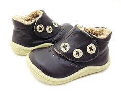 """We love the ever-stylish spat boot! For your baby boy or girl, London is our classic all-purpose boot, the very first of our vintage-inspired shoes. This boot's wide flap closure has three darling faux buttons made with cream leather and stitched with an """"X"""". Cut-out mini circles across the front add dimension and a plush teddy bear polyblend lines the inside of the boot."""